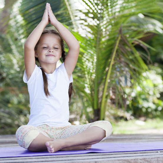 Child doing exercise on platform outdoors. Healthy ocean lifestyle. Yoga girl
